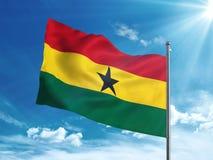 Флаг Ганы развевая в голубом небе Стоковое фото RF
