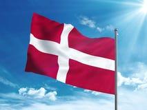 Флаг Дании развевая в голубом небе Стоковые Изображения