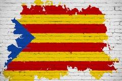 Флаг желтого цвета Каталонии, красная нашивка и звезда с акварелью брызгают влияние на белой предпосылке кирпичной стены, национа Стоковая Фотография