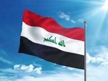 Флаг Ирака развевая в голубом небе Стоковое Изображение