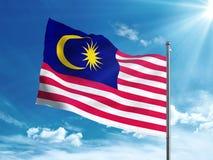 Флаг Малайзии развевая в голубом небе Стоковые Фотографии RF