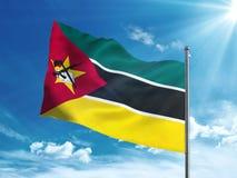 Флаг Мозамбика развевая в голубом небе Стоковое фото RF
