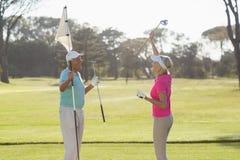 Флаг нося счастливых зрелых пар игрока гольфа Стоковое Фото