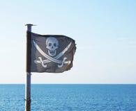 Флаг пирата с черепом и пересеченными шпагами Стоковая Фотография
