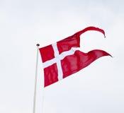 Флаг разделенный Danish развевая на светлой предпосылке Стоковое Фото