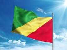 Флаг Республики Конго развевая в голубом небе Стоковое Изображение RF