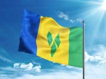 Флаг Сент-Винсент и Гренадины развевая в голубом небе Стоковое Изображение RF