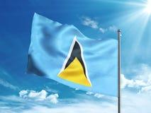 Флаг Сент-Люсия развевая в голубом небе Стоковое Изображение RF