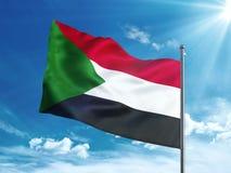 Флаг Судана развевая в голубом небе Стоковые Фото