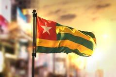 Флаг Того против предпосылки запачканной городом на backlight восхода солнца стоковое изображение rf