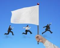 Флаг удерживания руки человека при бизнесмены бежать на сини Стоковые Фотографии RF
