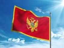 Флаг Черногории развевая в голубом небе Стоковые Изображения