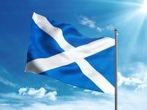 Флаг Шотландии развевая в голубом небе Стоковые Изображения