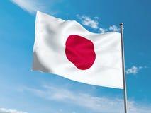 Флаг японца развевая в голубом небе Стоковая Фотография RF