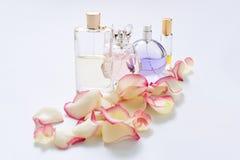 Флаконы духов с лепестками цветка на светлой предпосылке Парфюмерия, собрание благоуханием Аксессуары женщин Стоковые Изображения
