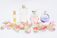 Флаконы духов с лепестками цветка на светлой предпосылке Парфюмерия, собрание благоуханием Аксессуары женщин Стоковое Изображение