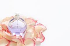 Флакон духов с лепестками цветка на светлой предпосылке Парфюмерия, собрание благоуханием Аксессуары женщин Copyspace для Стоковое Изображение RF