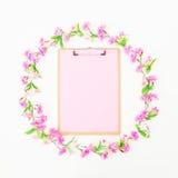 Флористическая круглая рамка сделанная из розовых цветков и доски сзажимом для бумаги на белой предпосылке Плоское положение, взг Стоковые Фотографии RF