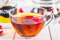 Флористический черный чай, чонсервная банка меда, лепестки на белом деревянном столе Стоковая Фотография RF