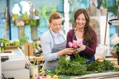 Флористы делая букет роз в магазине Стоковая Фотография