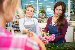 Флористы продавая розовый букет к клиенту в магазине Стоковое Изображение RF