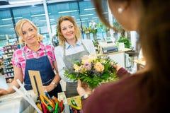Флористы продавая розовый букет к клиенту в магазине Стоковые Фотографии RF