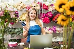 Флорист держа кредитную карточку в ее цветочном магазине Стоковые Фото