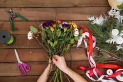 Флорист женщины создавая букет зимы Стоковые Фото