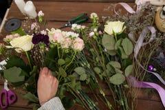 Флорист женщины создавая букет зимы Стоковое Изображение