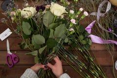 Флорист женщины создавая букет зимы Стоковая Фотография