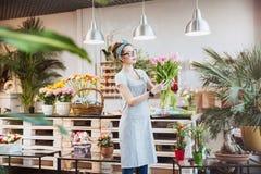 Флорист женщины стоя и держа пук розовых тюльпанов Стоковые Фото