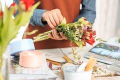 Флорист на работе: женские руки женщины делая модой современный букет из различных цветков Стоковая Фотография