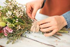 Флорист на работе: женские руки женщины делая модой современный букет из различных цветков Стоковая Фотография RF