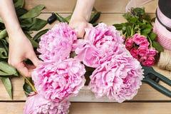 Флорист на работе: женщина делая флористическое украшение розовых пионов Стоковая Фотография