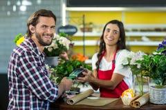 Флорист получая оплату кредитной карточкой от клиента в магазине флориста Стоковое фото RF