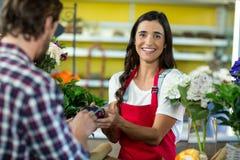 Флорист получая оплату кредитной карточкой от клиента в магазине флориста Стоковое Фото