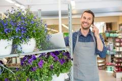 Флорист принимая заказ на мобильном телефоне в цветке Стоковая Фотография