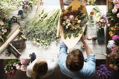 Флорист продавая расположение букета свежих цветков Стоковое Фото