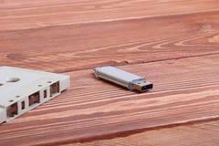 Флэш-диск и магнитофонная кассета на деревянной предпосылке Стоковое Изображение RF
