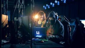 2 хакера работая с ноутбуком Злодеяние кибер и рубить концепция сток-видео