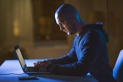 Хакер используя портативный компьютер для кибер атаки стоковые изображения rf