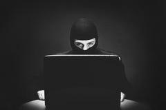 Хакер крадя данные по компьютера на ноче стоковое изображение