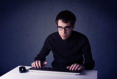 Хакер работая с клавиатурой на голубой предпосылке Стоковое фото RF