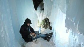 Хакер рубит сервера Человек, который нужно запрограммировать на компьтер-книжке в пещере льда Вокруг загадочного грота льда Челов видеоматериал