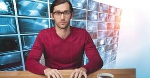 Хакер сидя на столе против мониторов в предпосылке Стоковая Фотография RF