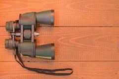 Хаки биноклей защитное на деревянной предпосылке, взгляд сверху Стоковые Фото