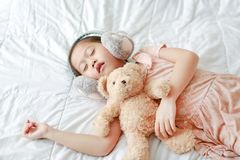 Халявы уха зимы милой маленькой азиатской девушки нося с плюшевым мишкой лежа на кровати дома стоковая фотография rf