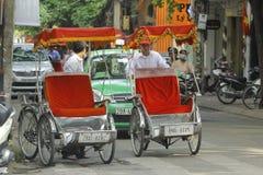 Ханой, Вьетнам: Жизнь в Вьетнаме Cyclo около озера шпаг в Ханое, Вьетнаме Cyclo туристский корабль farvourite ` s Стоковые Фотографии RF