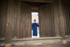 Ханой, Вьетнам - 22-ое июня 2017: Въетнамский человек с традиционный длинный раскрывать Ao Dai платья старый в общинном доме на т стоковое изображение rf
