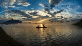 Ханой, Вьетнам - 12-ое июня 2016: Озеро Дун Mo при несколько fishers улавливая рыб сетчатой ловушкой в красивом периоде захода со Стоковые Изображения